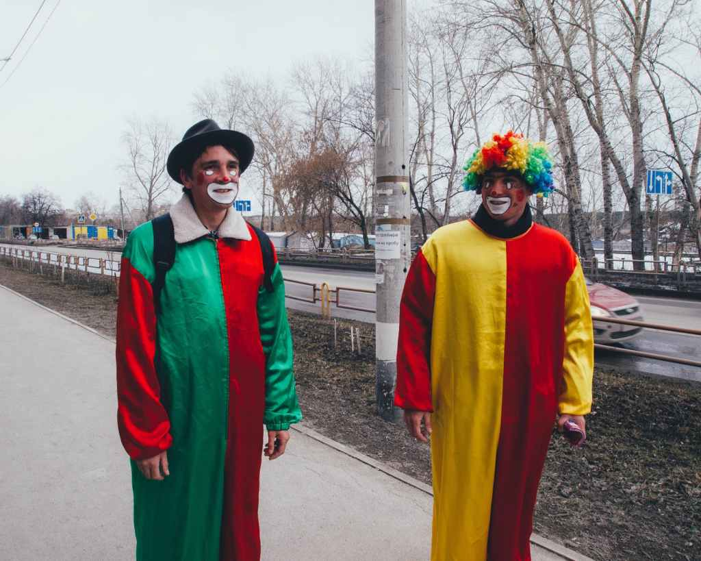 photography of two clowns in the street